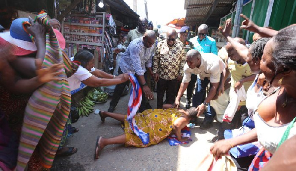 A woman lying on the floor to 'worship' Nana Addo