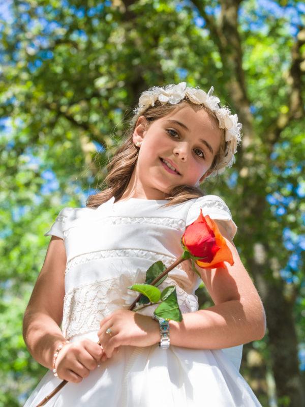 Fotografía de comunión-nena vestida con traxe branco e flor bermella.