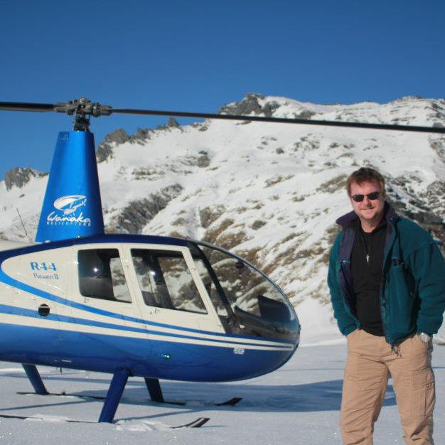 Adam Starr the flight instructor stands next to a blue and white helicopter in front of a snowy mountain