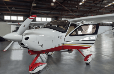 The Tecnam P2008 plane coloured red, black, and white, doors open, inside a plane hangar