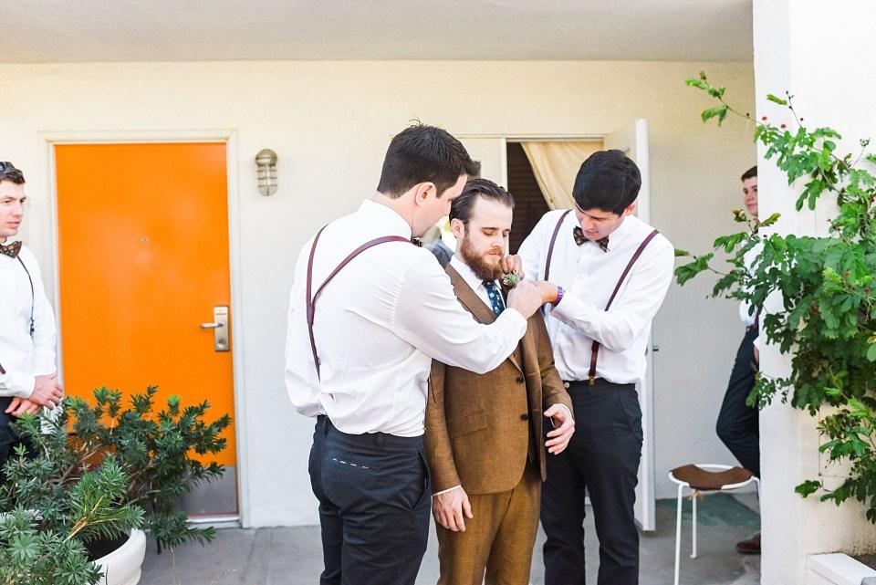 groom getting help from groomsmen to get dressed
