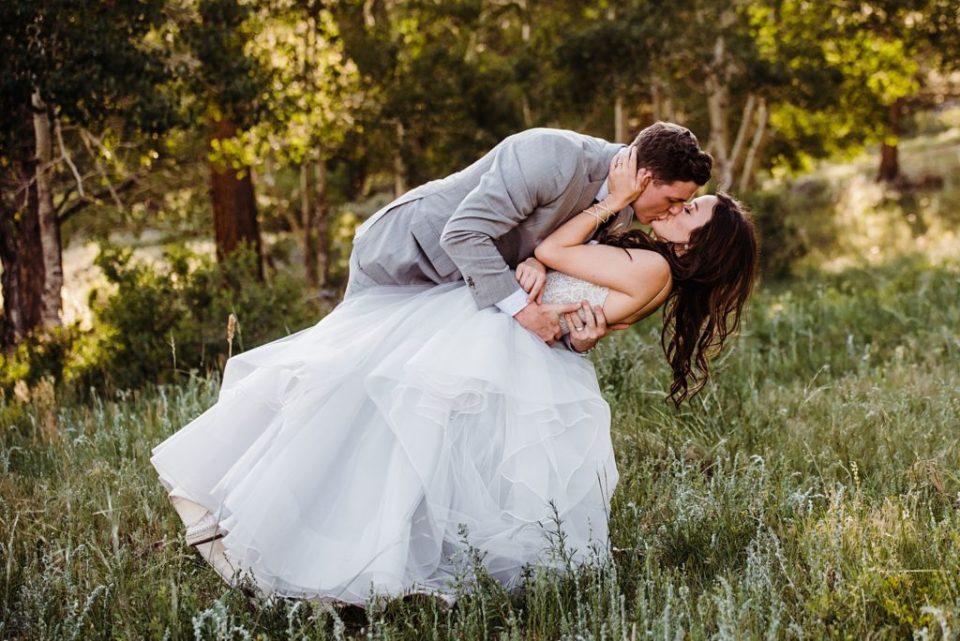 groom dipping bride estes park wedding photo
