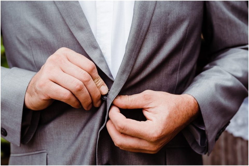 groom buttoning up his jacket