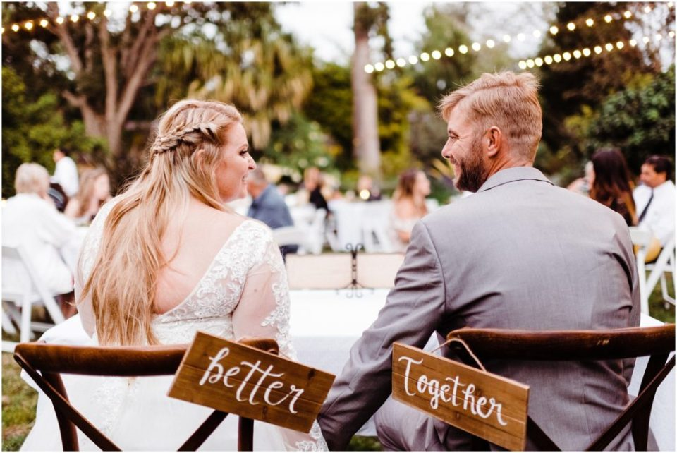 bride and groom with better together sign
