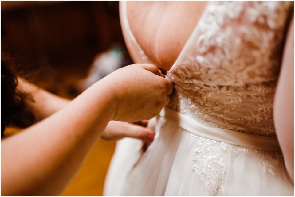 zipping up the brides dress