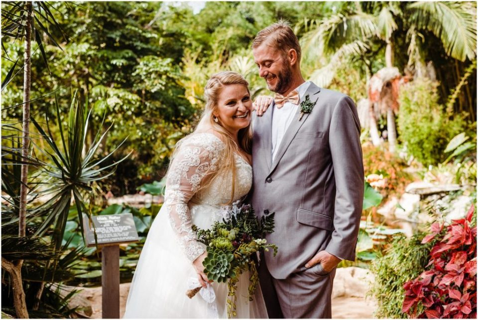 bride and groom laughing together in a botanic garden