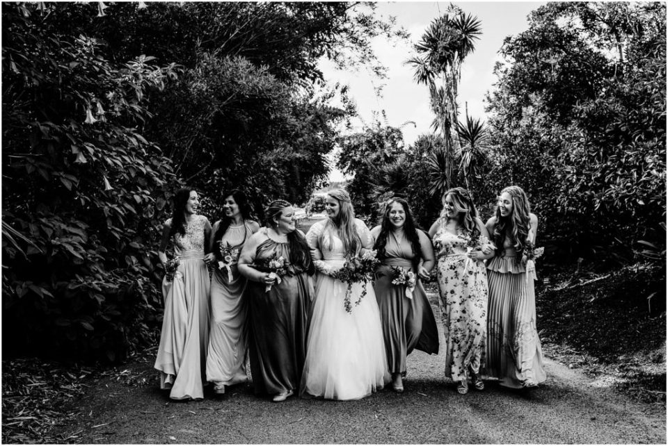 black and white bridal party portrait in a botanic garden