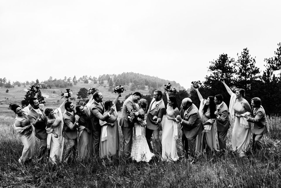 black and white photo of wedding party cheering on bride and groom