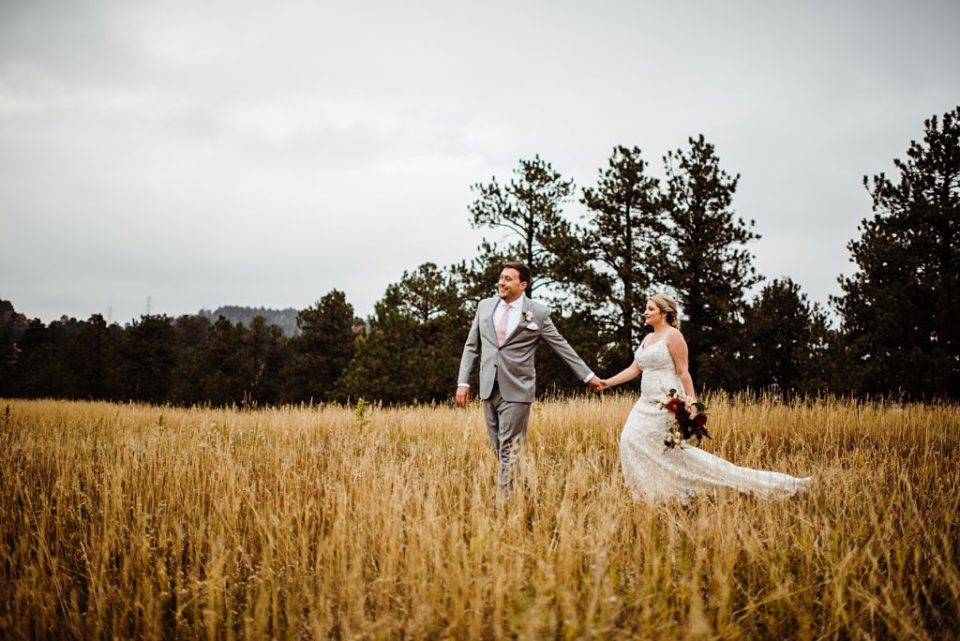 bride and groom walking through a field in golden