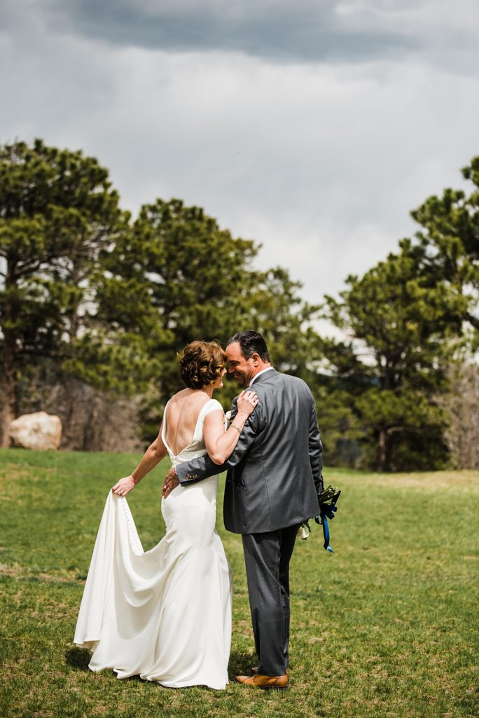 bride and groom kissing from behind