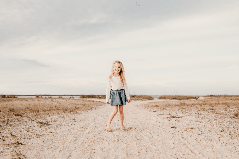 little girl twirling in the sand
