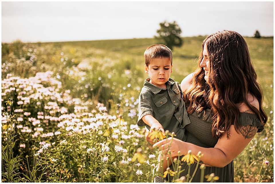 little boy held by mom looking at wildflowers