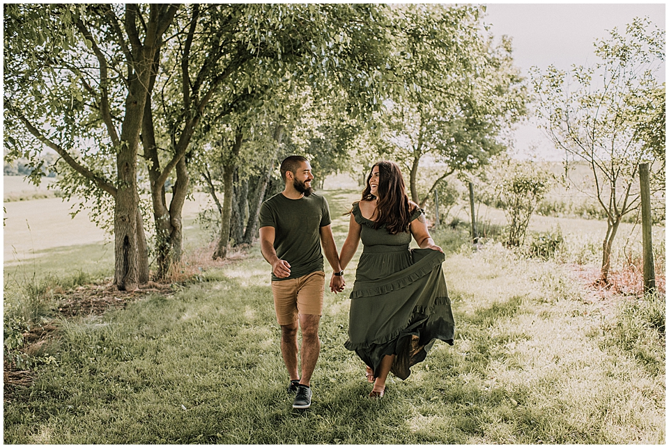 couple running together in a grove of trees
