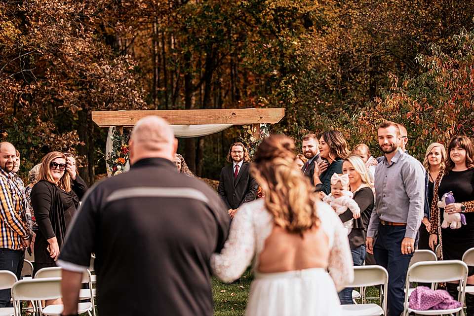 groom watching as bride walks down the aisle with her dad