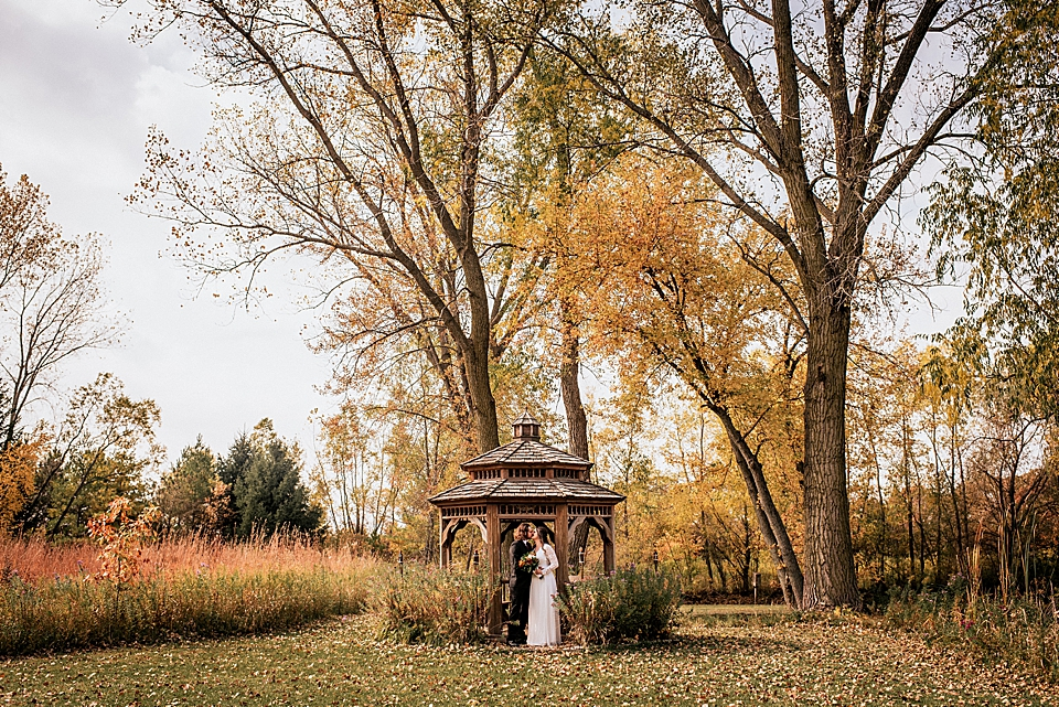 bride and groom in wood gazebo in the fall in wisconsin