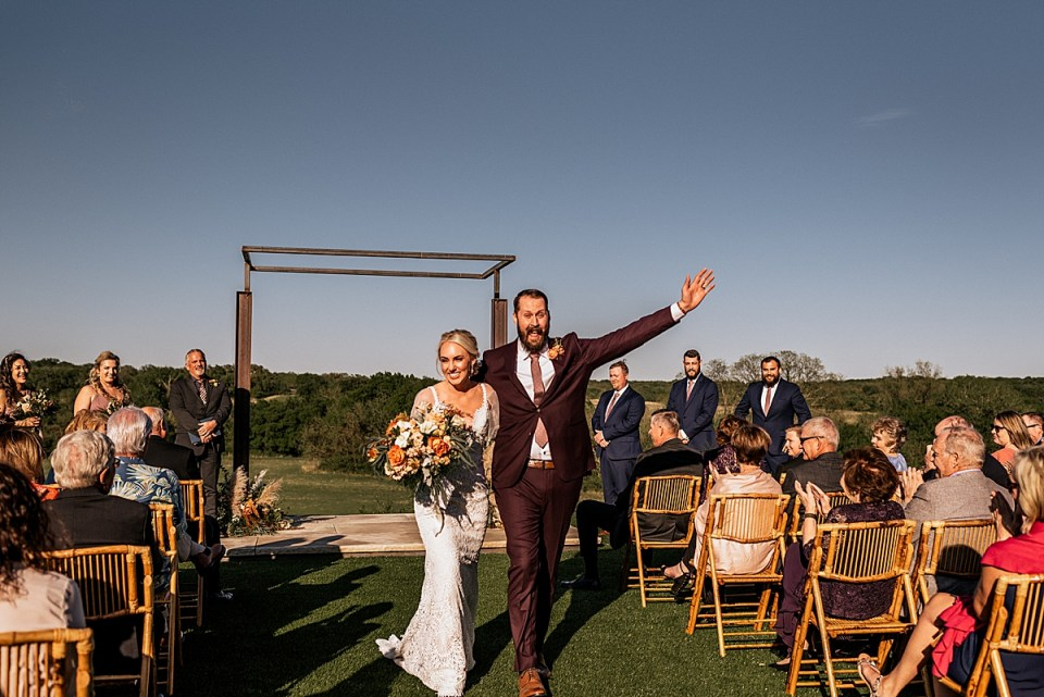 excited bride and groom ceremony recessional