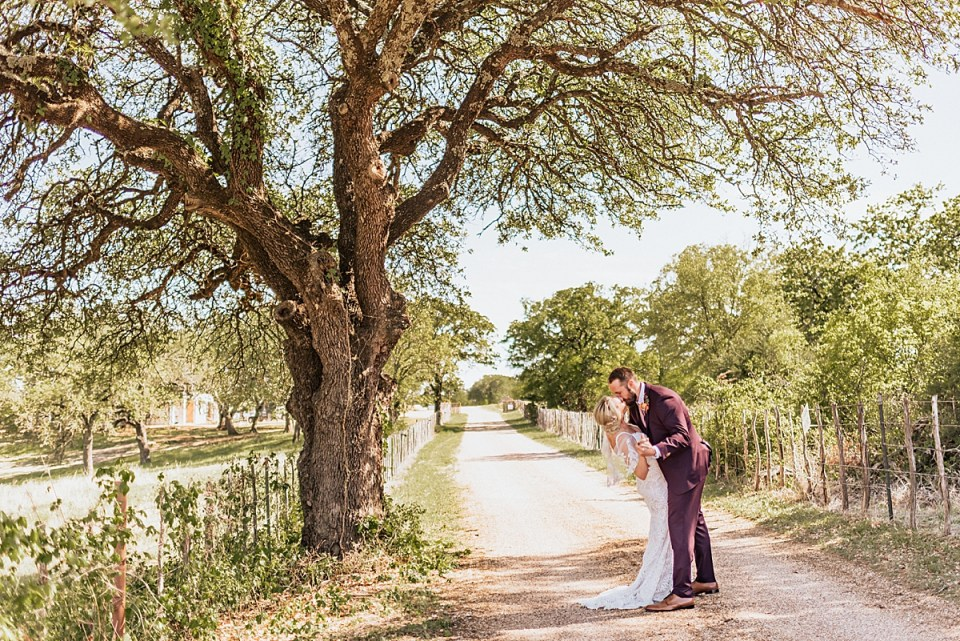groom dipping bride for a kiss on a dirt path under a large tree