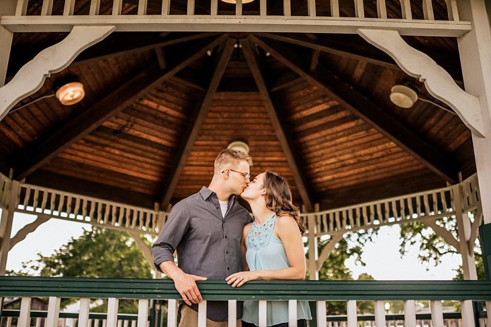 engaged couple kissing underneath gazebo for downtown burlington engagement session