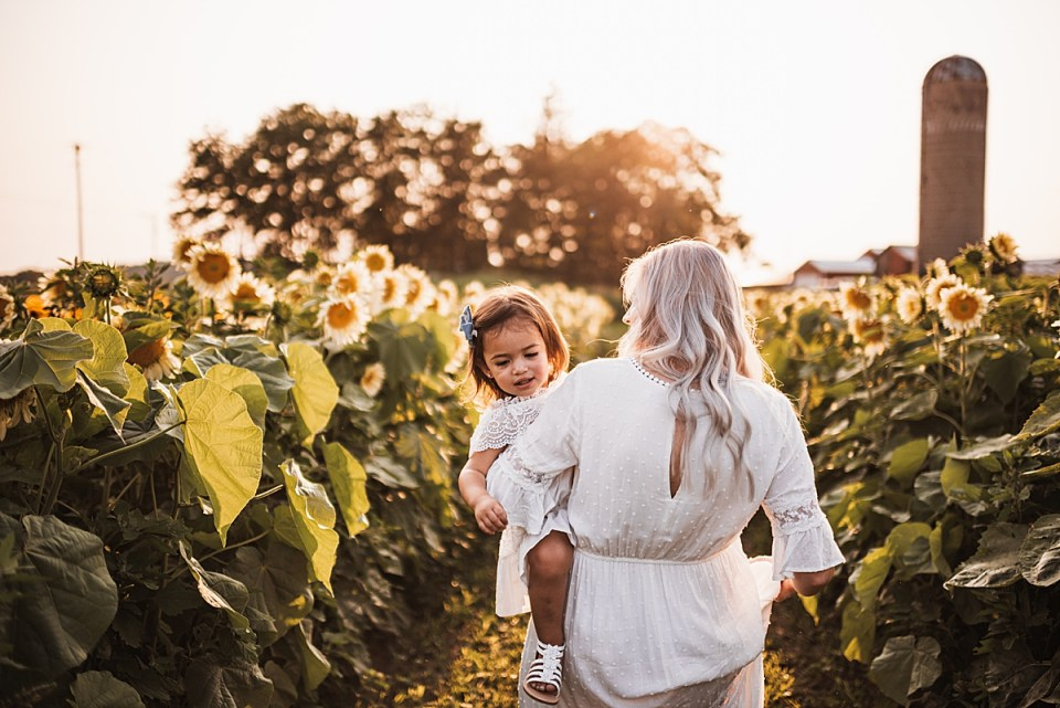mom and toddler walking through a flower field