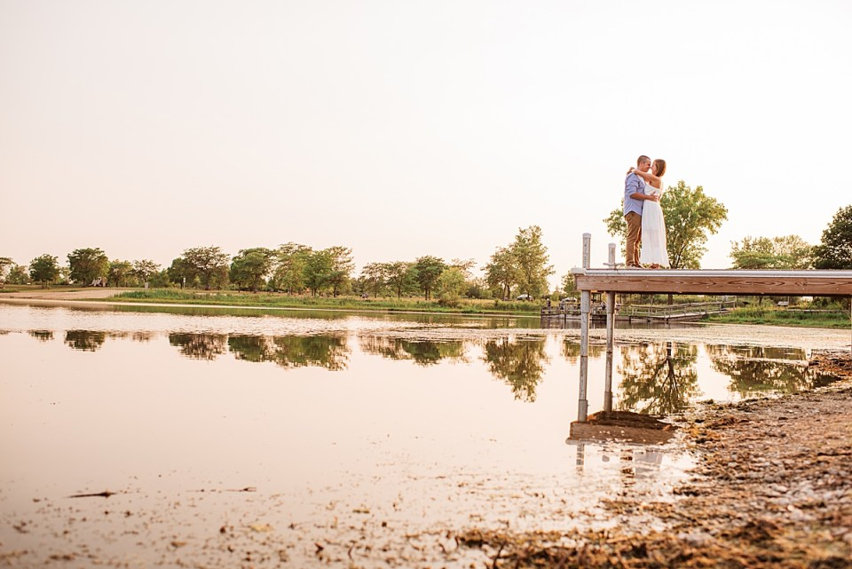 engaged couple standing at the end of a pier kissing