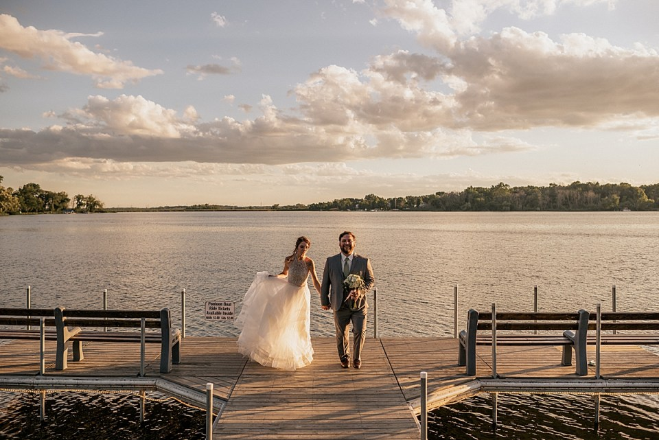 bride and groom at the end of the pier at the lake at sunset