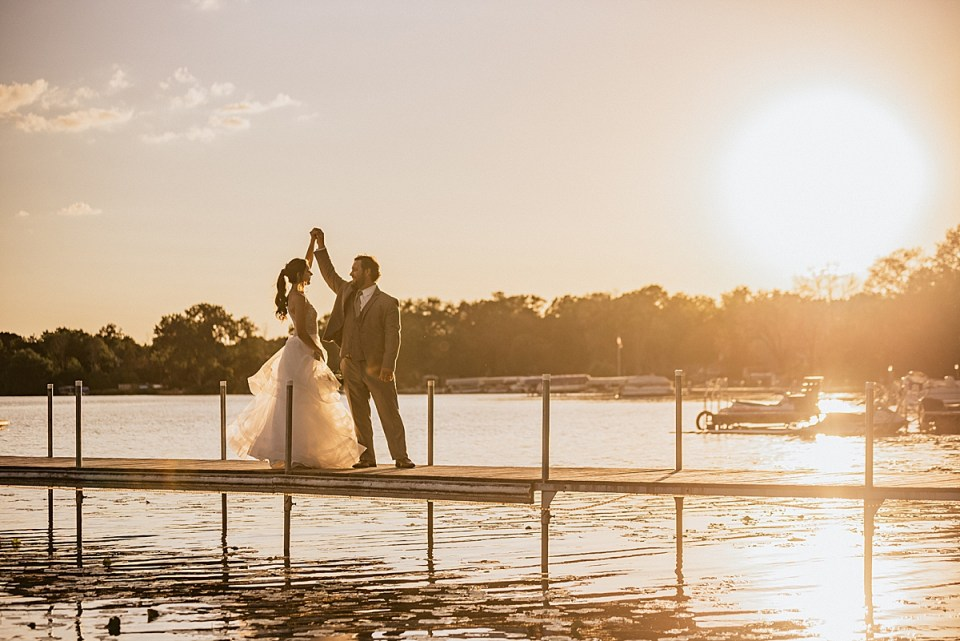 bride and groom dancing on the lake pier at sunset