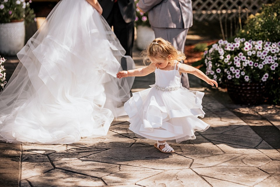 little girl twirling during wedding ceremony