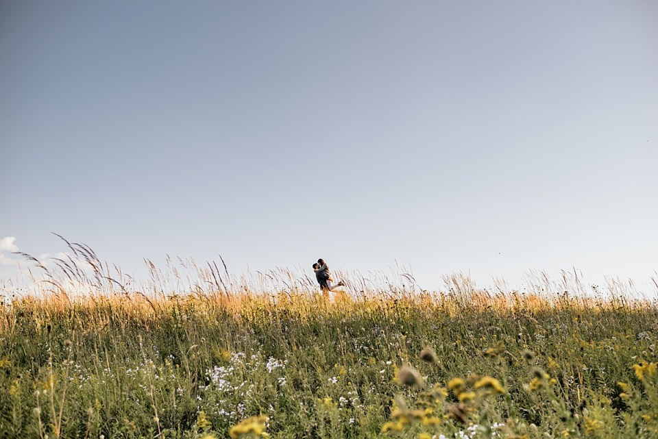 engaged couple walking together through a field of wildflowers at white river county park