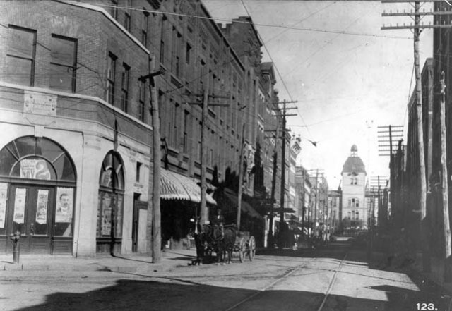 View up Patton Ave from Haywood St toward the square. Courthouse (1876) with bell tower in background. Paragon Bldg at left, on the corner. Black man driving a wagon sitting in front of the dentist's office. Street car tracks in the unpaved street. Drhumor Bldg built 1895 on right. Estimated date 1895-1898. From T. H. Lindsey, Scenes of Western North Carolina. Pack Memorial Public Library