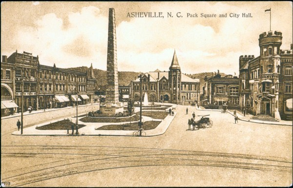 Pack Square around 1900, with Vance Monument in middle and streetcar tracks in foreground. Pack Memorial Public Library.
