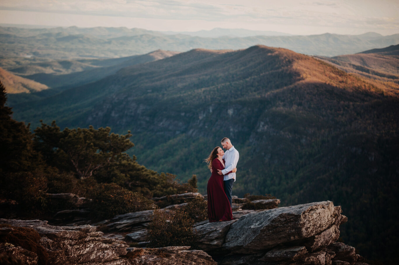 Engaged couple embraces on a mountain top in Asheville, NC for their Engagement Photo Session.