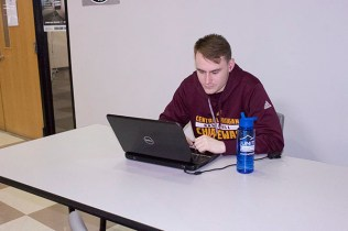 Senior, Joel Dyer, studies in between weight lifting and practice to keep his head strong.