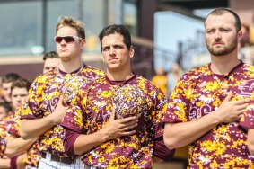 Baseball players, Cameron Miller and Michael Brettell, stand for the national anthem during their game against Western Michigan University.