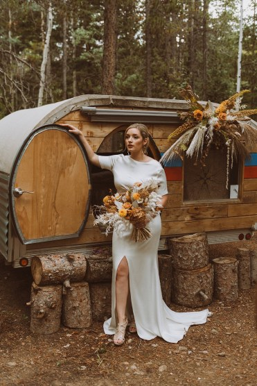 Bride standing with her bouquet in front of a teardrop trailer at Treehaus CO | Wedding portraits | Elopement portraits | Bride and groom elopement photos | Elopement wedding photos in Colorado | Colorado wedding photos | Colorado elopement photos | Elopement at Treehaus, Colorado |  Treehaus Colorado | Colorado elopement | Treehaus elopement | Colorado elopement venue | Colorado mountain elopement venue | Unique elopement venue | Elopement venue in Colorado | Ashley Joyce Photography 2020