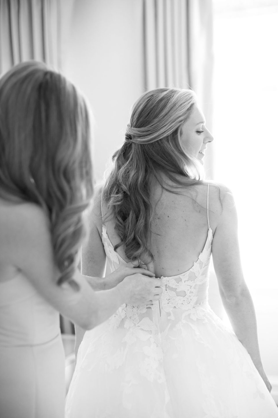 bride gets into wedding gown photographed by Ashley Mac Photographs