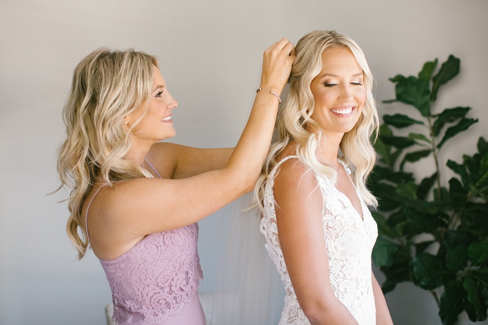 bridesmaid helps bride with veil before Rumson Country Club Riverhouse wedding with Ashley Mac Photographs