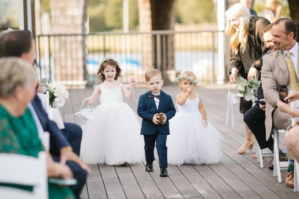 flower girls and ring bearers walk down aisle at Rumson Country Club Riverhouse with Ashley Mac Photographs