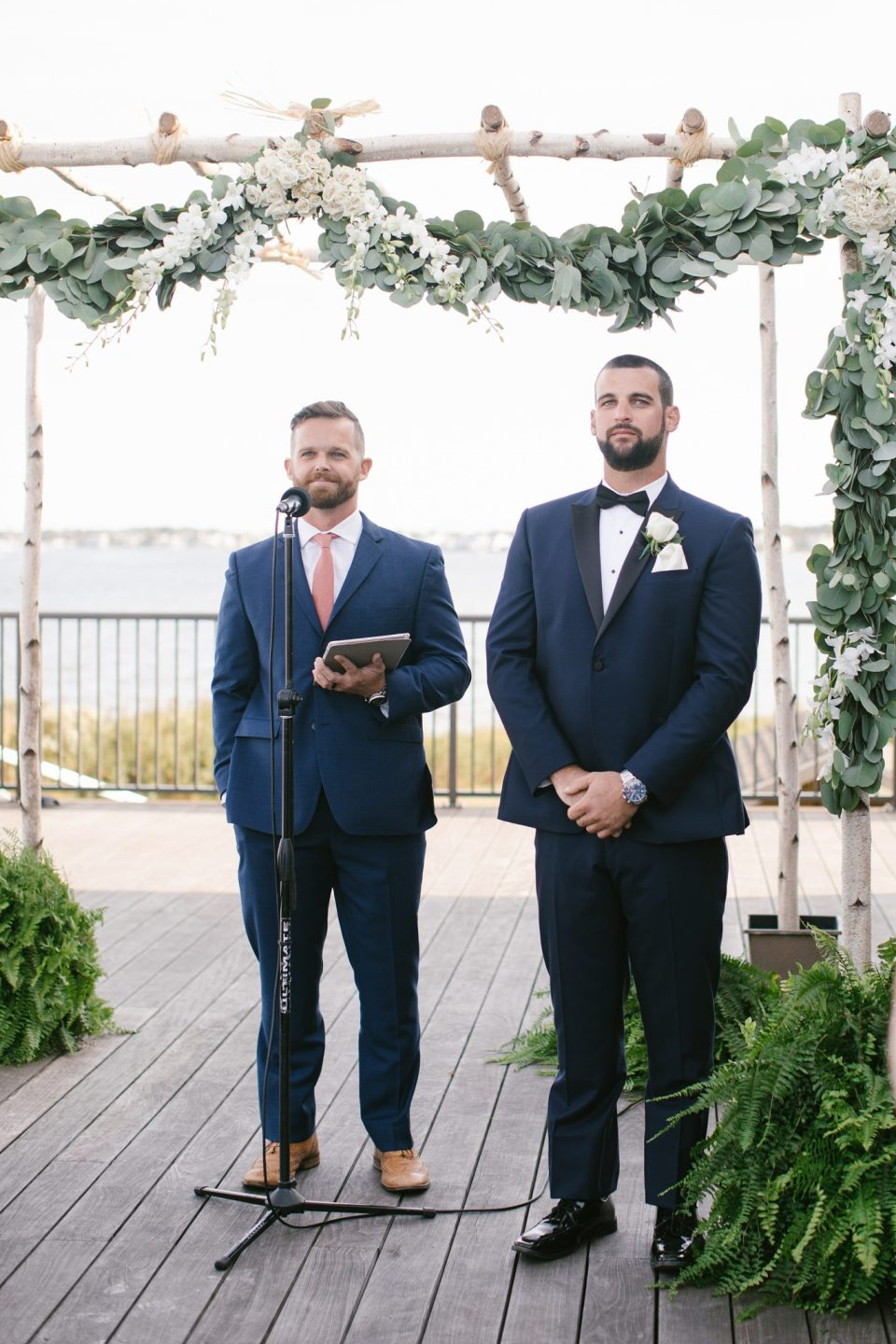 groom watches bride walk down aisle during Rumson Country Club Riverhouse wedding ceremony