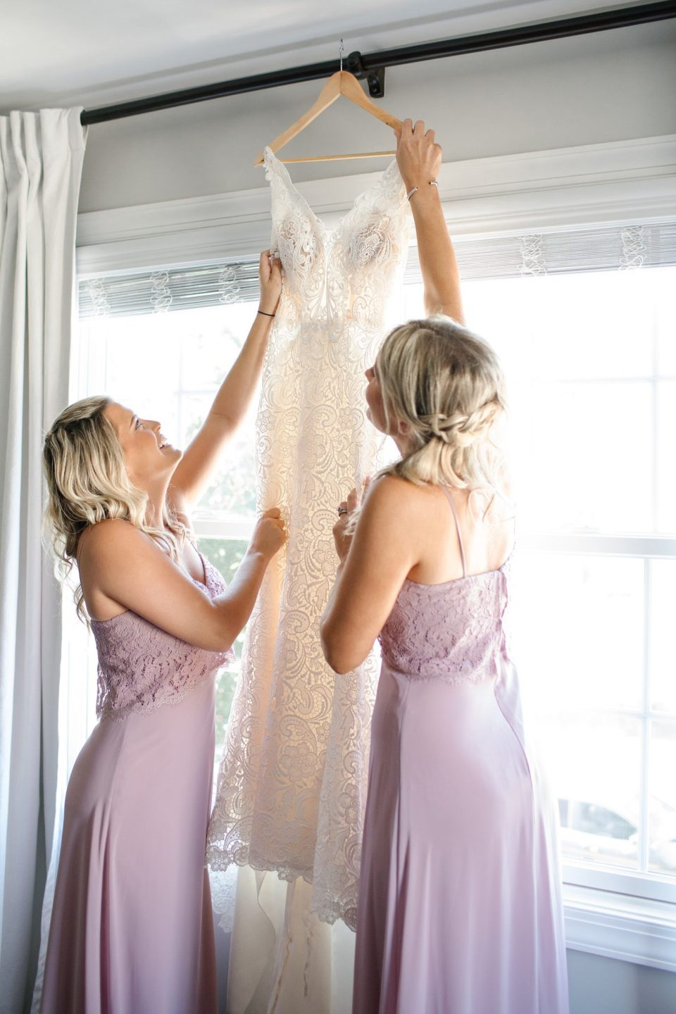 bridal party prepares dress for the bride with Ashley Mac Photographs