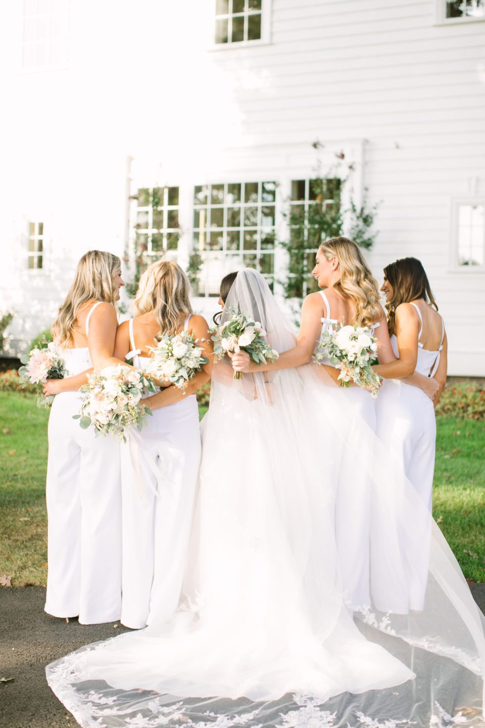 bridesmaids in white jumpsuits hug bride photographed by Ashley Mac Photographs