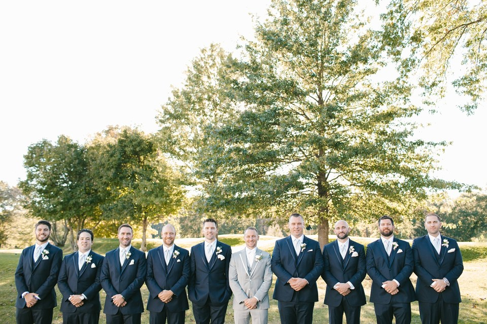 groomsmen pose in navy suits for Ashley Mac Photographs