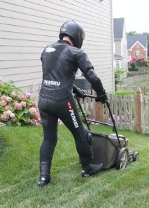 Man mowing lawn in full motorcycle safety gear