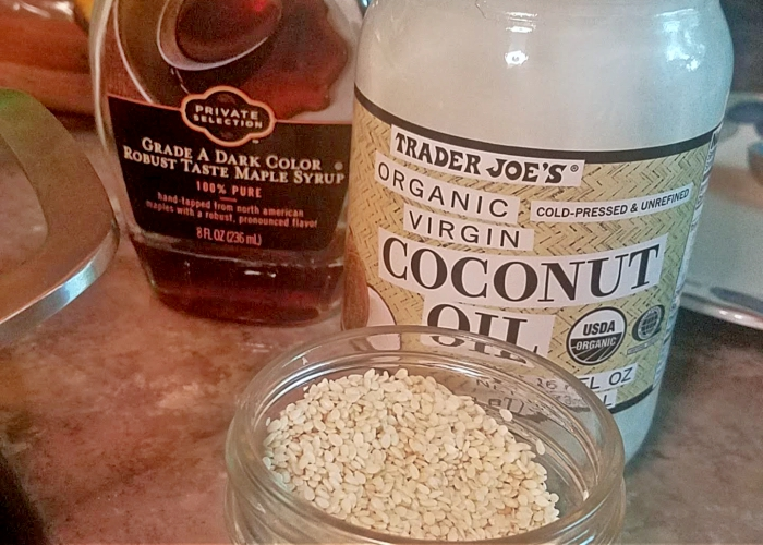 maple syrup, coconut oil, and sesame seeds in a jar, on a counter