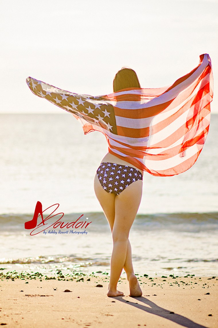 silhouette of girl through american flag on beach