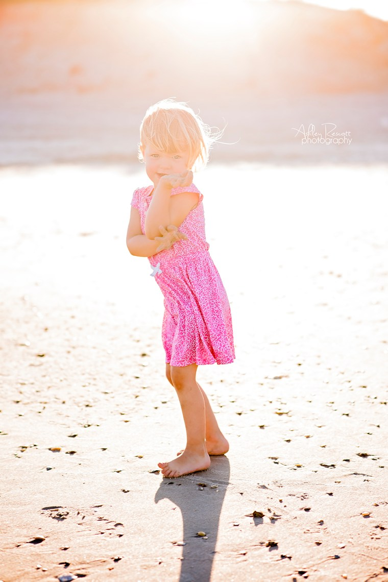 toddler girl on the beach in a pink dress