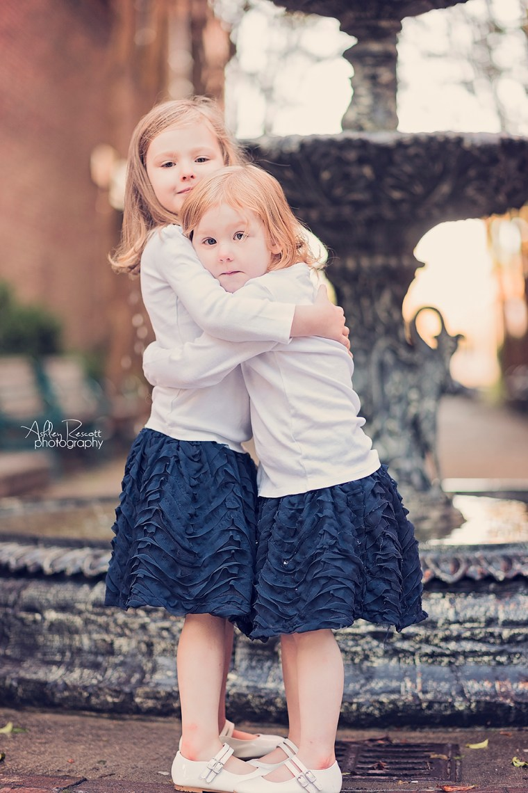 sisters hugging in front of fountain in new bern nc