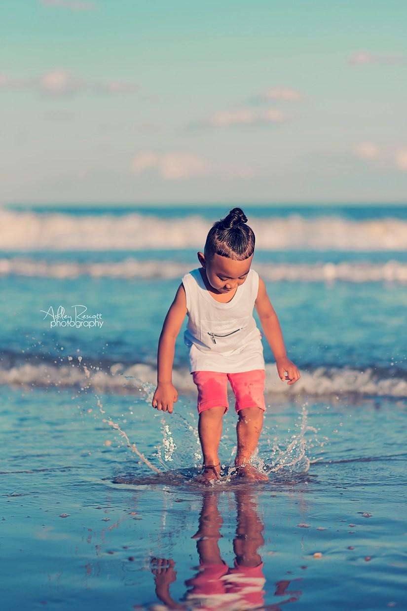 little boy splashing in ocean