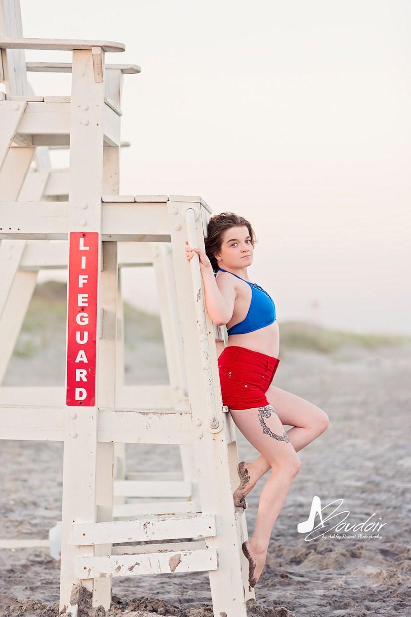 woman standing on lifeguard chair on beach