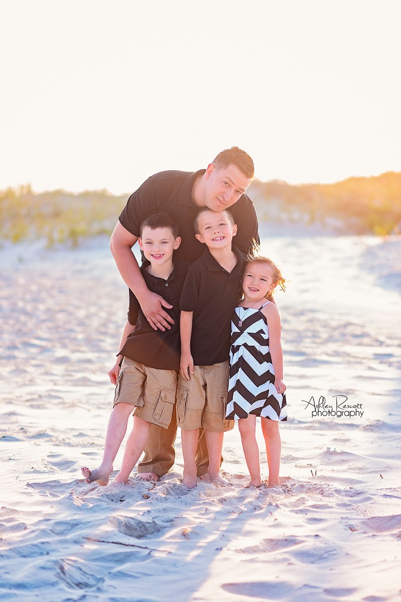 family in front of sand dunes on beach