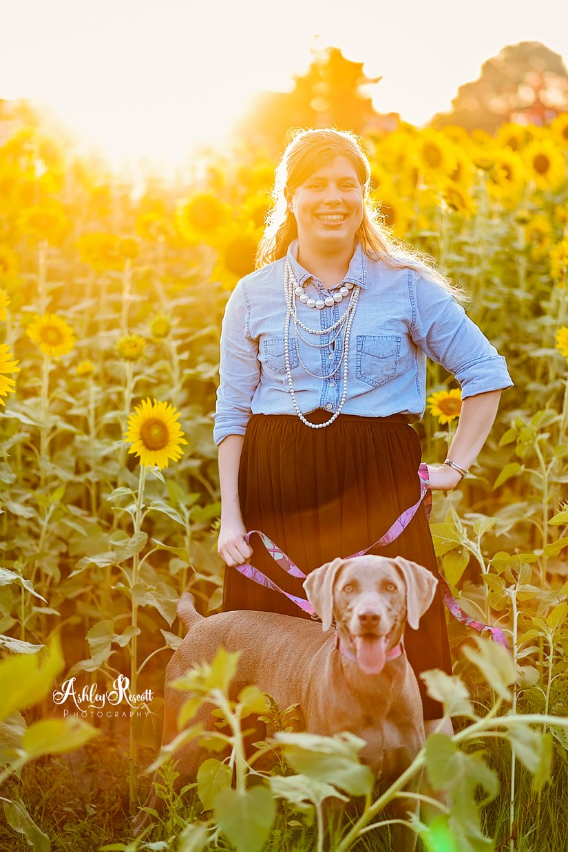 woman with her dog in a sunflower field